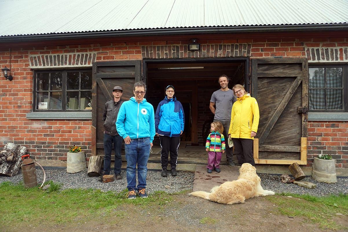 Kuusi ihmistä ja koira seisovat vanhan tallirakennuksen edessä.
