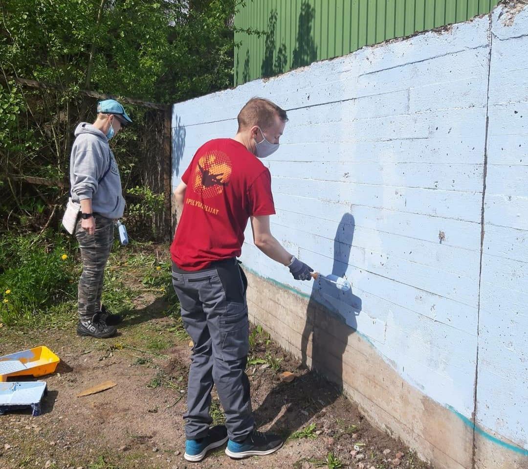 Kaksi henkilöä maalaamassa muraalia seinää vaaleansinisellä maalilla.