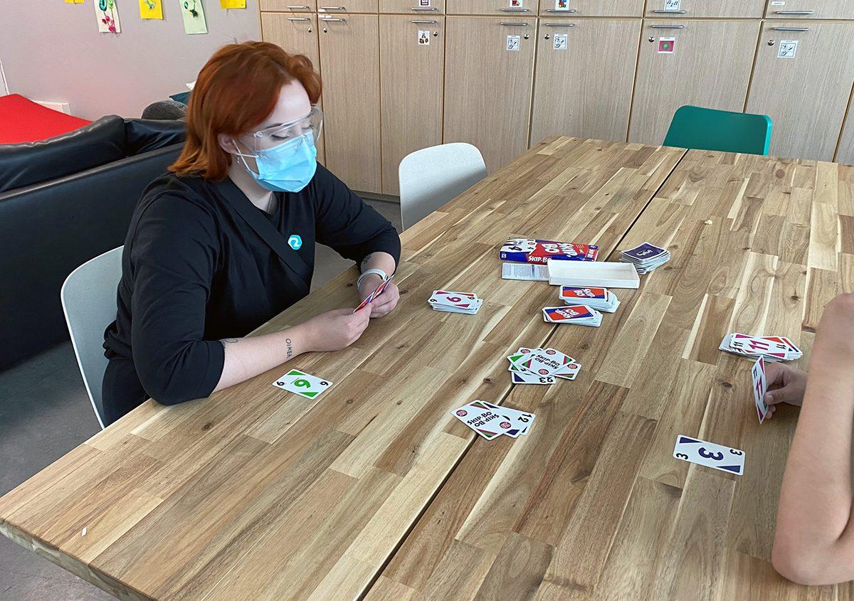 Naisohjaaja pelaa uno-korttipeliä nuoren kanssa pöydän äärellä.