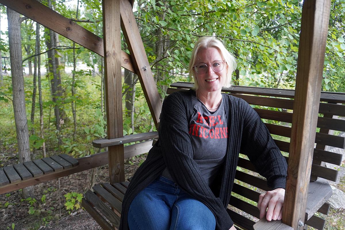 Liina Sievers istuu keinussa vihreiden puiden alla.